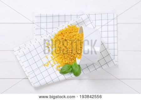 bowl of small pasta shells spilt out on checkered dishtowel