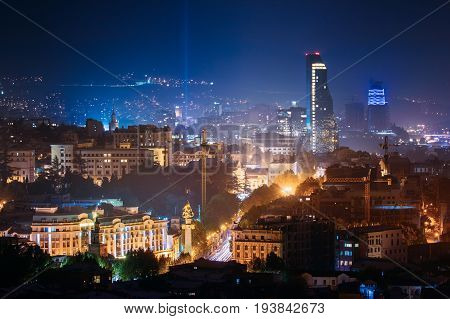 Tbilisi, Georgia. Construction Development Of Modern Architecture On Background Of Urban Night Cityscape. Evening Night Scenic Aerial View Of City Center. Freedom Square And Shota Rustaveli Ave