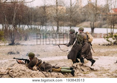 Gomel, Belarus - November 26, 2016: Re-enactors Dressed As Red Army Russian Soldiers Of WWII Running On Battlefield. Celebration Of 73rd Anniversary Of Liberation Of Gomel From Nazi Invaders