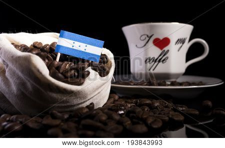 Honduras Flag In A Bag With Coffee Beans Isolated On Black Background