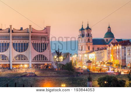 Grodno, Belarus - June 9, 2017: Grodno Regional Drama Theatre, St. Francis Xavier Cathedral And Traffic In Mostowaja And Kirova Streets At Evening In Night Illuminations Lights. Sunset Sky