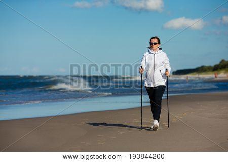 Nordic walking - woman training on beach
