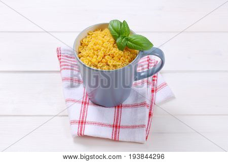 cup of small pasta shells on on checkered dishtowel