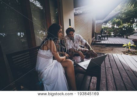 Young couple: serious white woman looking on screen of modern laptop while her colleague pointing and explaining something to her both sitting at the table on veranda of country house on summer day