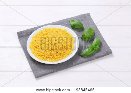 plate of small pasta shells on grey place mat