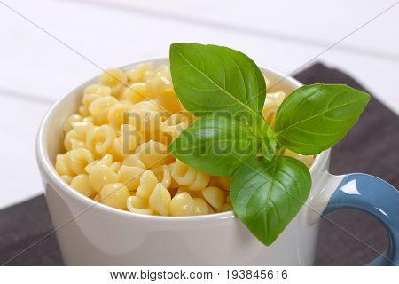 mug of small pasta shells on dark grey place mat - close up