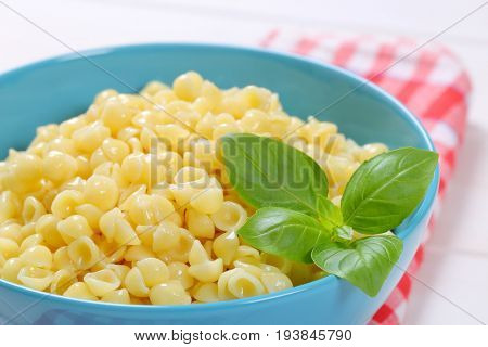 bowl of small pasta shells on checkered dishtowel - close up