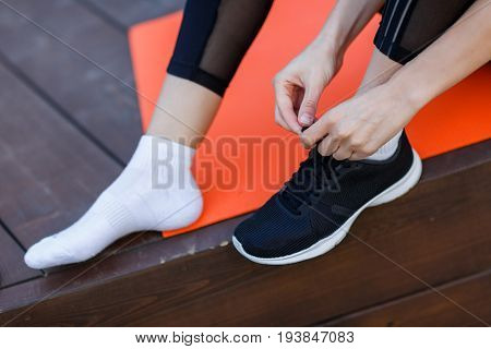 Sportswoman ties shoelaces on sneaker in gym, sitting on rug on wooden floor