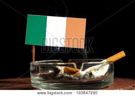 Irish Flag With Burning Cigarette In Ashtray Isolated On Black Background