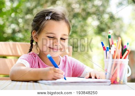 Little Girl Is Drawing Picture Outdoors In Summer