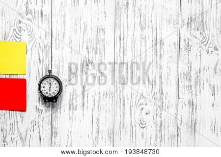 Football refereeing. Yellow and red referee cards, stopwatch, pad, on wooden background top view.