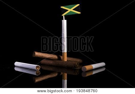 Jamaican Flag With Cigarettes And Cigars. Tobacco Industry Concept.