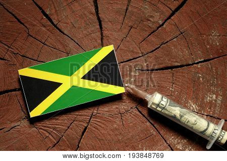 Jamaican Flag On A Stump With Syringe Injecting Money In Flag