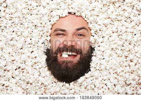 From above view of bearded man grimacing and looking at camera all covered with popcorn,