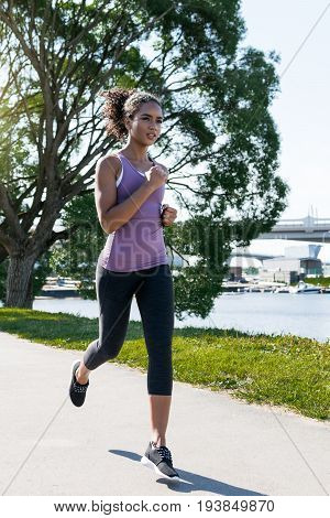 Young female jogger doing exercising outdoors in park