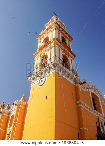 Bright yellow facade of the San Apostolo church in the Zocalo in Cholula Mexico viewed across lawns and shrubs against a blue sky