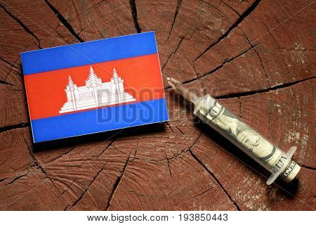 Cambodian Flag On A Stump With Syringe Injecting Money In Flag