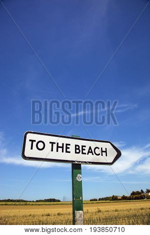 In the countryside a road sign with the inscription to the beach. with a blue sky and a field in the background