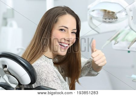 Patient with perfect white teeth and smile satisfied after dental treatment in a dentist office with medical equipment in the background