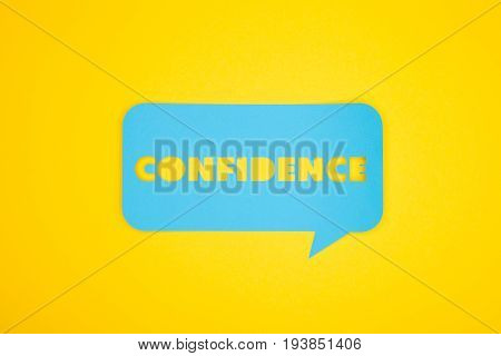 Horizontal studio shot of confidence word cut-out in blue bubble on the yellow background.
