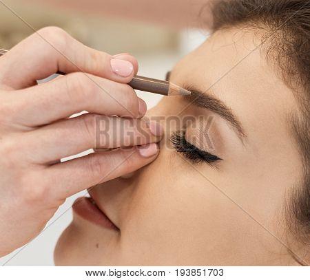 Young woman getting professional makeup at makeup artist.