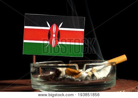 Kenyan Flag With Burning Cigarette In Ashtray Isolated On Black Background