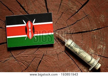 Kenyan Flag On A Stump With Syringe Injecting Money In Flag