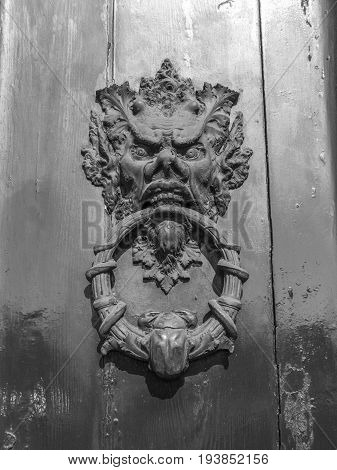 the devil on an ancient door of an ancient building