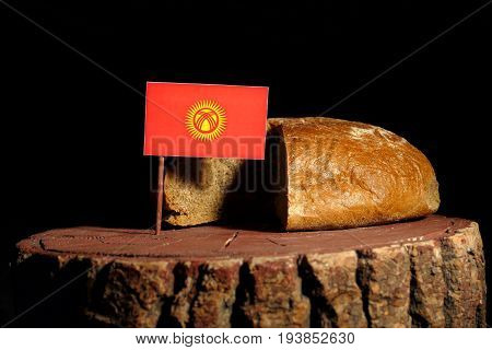 Kyrgyzstani Flag On A Stump With Bread Isolated