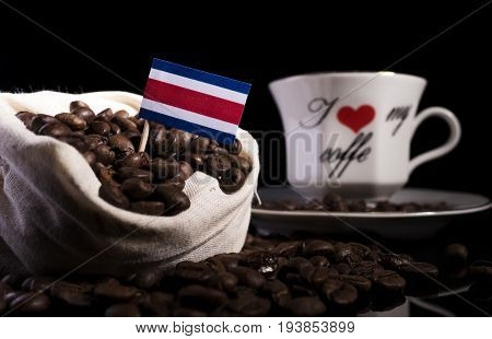 Costa Rican Flag In A Bag With Coffee Beans Isolated On Black Background