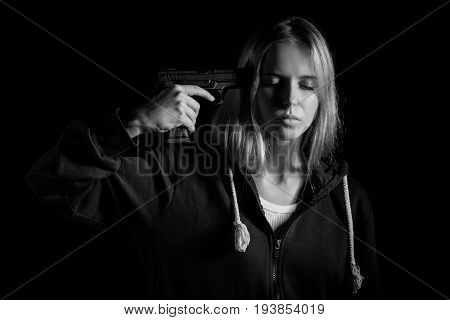 serious girl shooting herself on black background, monochrome