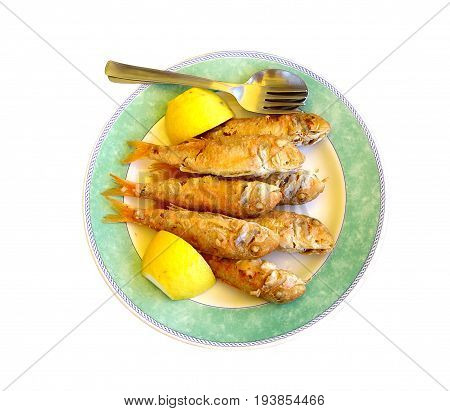Plate of fried mullet with lemon a fork and a spoon on a white background