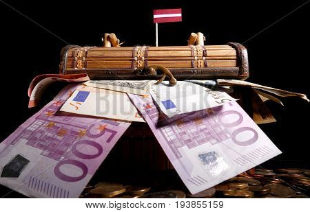 Latvian Flag On Top Of Crate Full Of Money