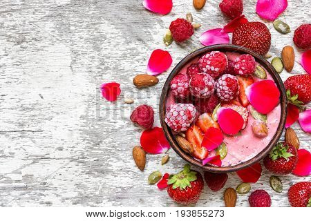 bowl of homemade pink smoothie with fresh raspberries strawberries nuts seeds and roses flowers petals over white wooden background. top view. healthy breakfast
