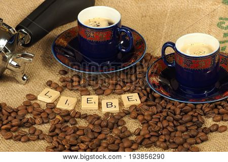 Melbourne, Australia - June 24, 2017: Coffee beans, two ornate cups and a group handle with wooden letter tiles arranged to form the word