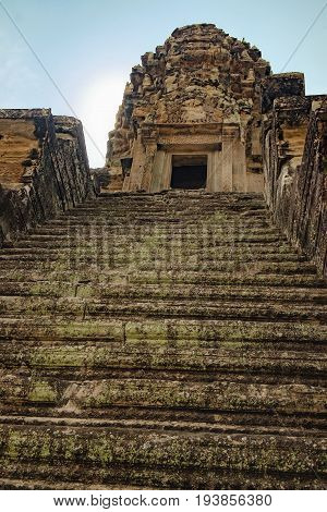 Stone old steps covered with moss to the top of the Angkor Wat stone tower, Siem Reap, Cambodia.