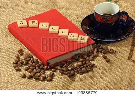 Melbourne, Australia - June 24, 2017: Coffee beans, a cup and a red book with wooden letter tiles on the book arranged to form the word