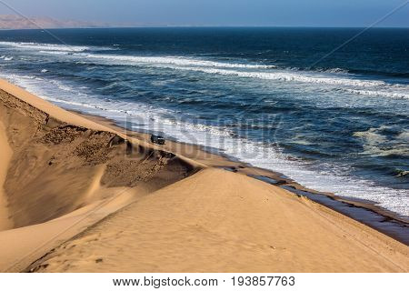 Jeep - safari through the huge sand dunes. Ocean surf with foamy waves. Atlantic coast of Walvis Bay, Namibia, south of Africa. The concept of extreme and exotic tourism