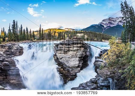 The full-water bubbling waterfall of Athabasca.  The concept of extreme and ecological tourism. Clear autumn evening in Jasper National Park. Cold blue water at sunset