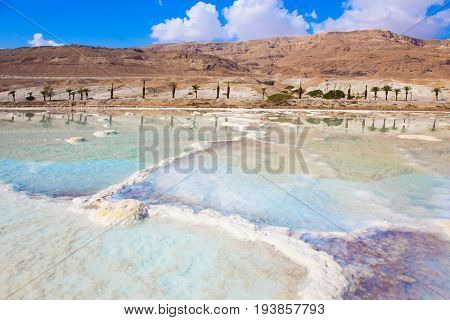 The concept of medical and ecological tourism. Reduced water in the salty Dead Sea, Israel. The evaporated salt has developed into fantastic patterns