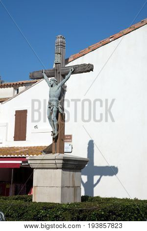 Huge crucifix on a pedestal in a town square. Sunny spring day. Morning carnival in the Saintes-Maries-de-la-Mer, Provence. The concept of ethnographic tourism