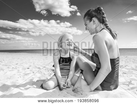 Smiling Mother And Daughter On Seacoast Applying Sun Cream