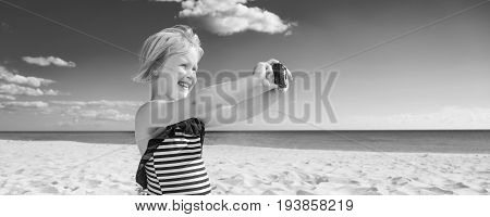 Happy Blond Child On Seacoast Taking Photo With Digital Camera