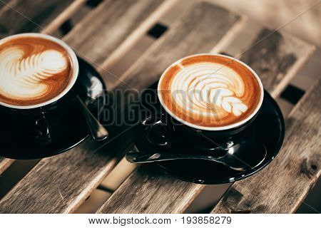 Two cups of cappuccino with latte art in black cups on wooden table. Morning coffee for couple in love. Top view.