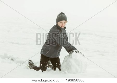 Boy Forming A Large Snowball Outside