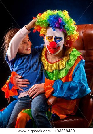 Single parent family. Tired mom after work as clown on birthday on dark background. Adult child relationship. Social problem mad parent. Unloved work idea.