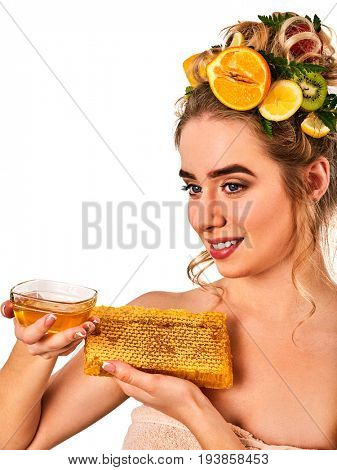 Honey facial mask with fresh fruits for hair and skin on woman head. Girl face hold honeycombs for homemade organic skin and hair therapy. Concept of healthy and beauty medicinal properties of honey.