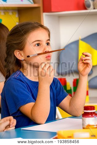 Small student painting in art school class. Child drawing by paints on table girl in kindergarten. Kid does not know what to draw