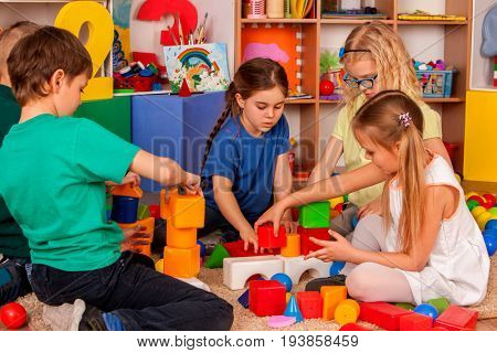 Children building blocks in kindergarten. Group kids playing toy on floor in interior preschool. Building tower of cubes. Independent children's creativity