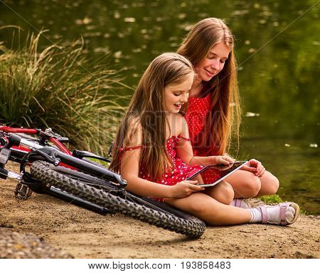 Bikes cycling kids. Girl recreation near bicycle into park. Children watch tablet pc. Girl in ecotourism. Older sister shows younger new game on pc tablet sitting near water. Friendly family.